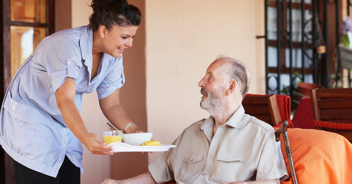 A Senior Receiving A Home Cooked Meal From A Home Care Aide