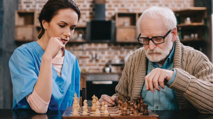 Image Of A Home Health Nurse Playing A Game With A Medicare Patient.
